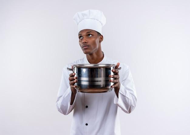 Junge verwirrte afroamerikanische köchin in der kochuniform hält topf mit beiden händen auf isolierter weißer wand