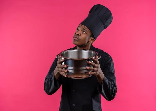 Junge verwirrte afroamerikanische köchin in der kochuniform hält topf und schaut isoliert auf rosa wand