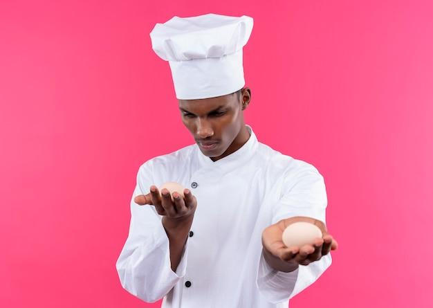 Junge verwirrte afroamerikanische köchin in der kochuniform hält und betrachtet eier in beiden händen lokalisiert auf rosa wand