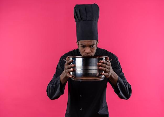 Junge verwirrte afroamerikanische köchin in der kochuniform hält und betrachtet topf lokalisiert auf rosa wand