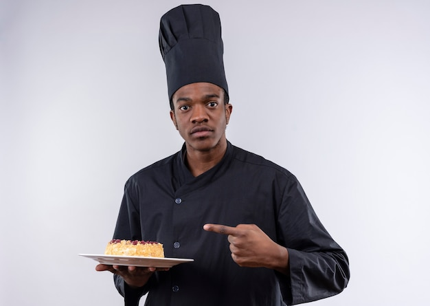 Junge verwirrte afroamerikanische köchin in der kochuniform hält und zeigt auf kuchen auf teller lokalisiert auf weißer wand