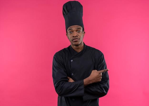 Junge verwirrte afroamerikanische köchin in der kochuniform zeigt auf die seite, die auf rosa wand lokalisiert wird