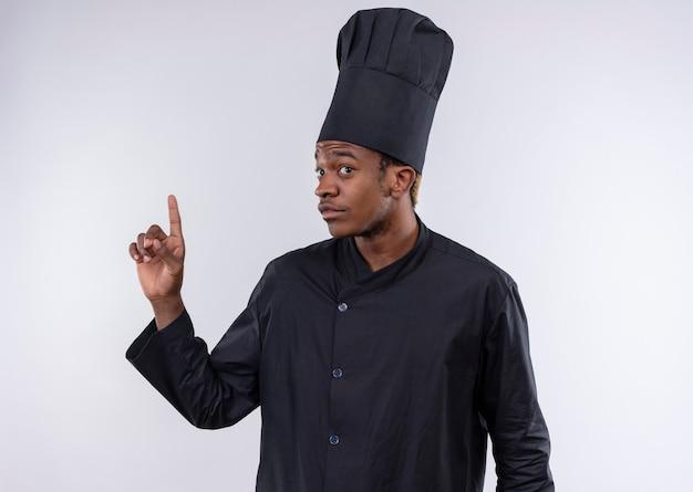 Junge verwirrte afroamerikanische köchin in der kochuniform zeigt lokalisiert auf weißer wand