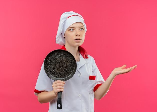 Junge verwirrte blonde köchin in kochuniform hält bratpfanne und schaut zur seite isoliert auf rosa wand