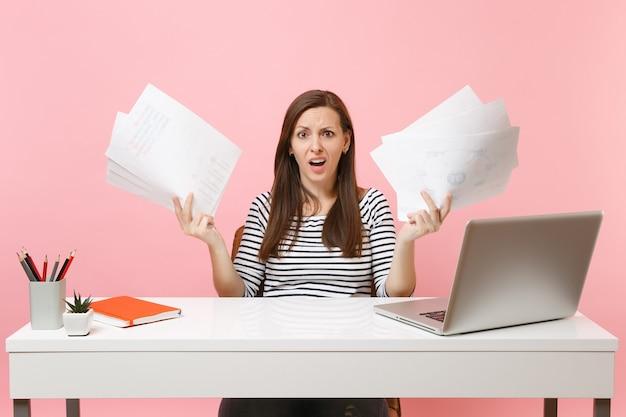 Junge verwirrte frau, die hände mit papierdokumenten ausbreitet, an einem projekt arbeitet, während sie mit laptop im büro sitzt office