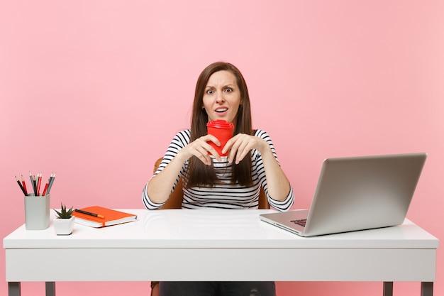 Junge verwirrte frau in ratlosigkeit, die eine tasse kaffee oder tee hält und an einem projekt arbeitet, das im büro sitzt, mit einem pc-laptop einzeln auf pastellrosa hintergrund. erfolgsgeschäftskarrierekonzept. platz kopieren.