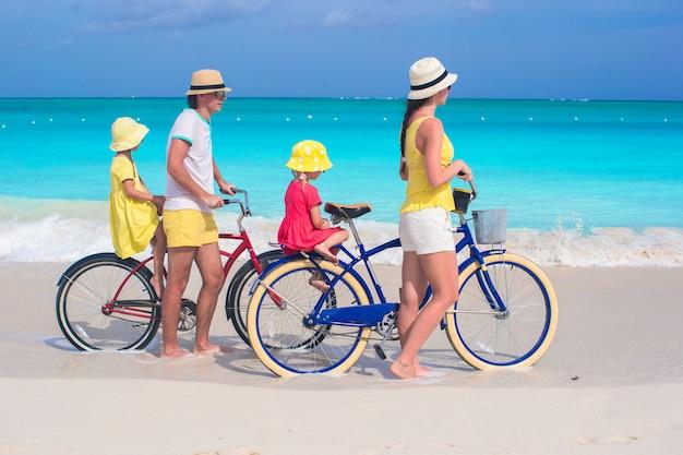 Junge vierköpfige familie, die fahrrad auf einen tropischen sandstrand fährt