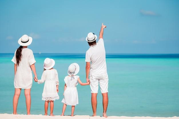 Junge vierköpfige familie im weiß auf tropischem strand. eltern mit zwei kleinen kindern, die das meer betrachten