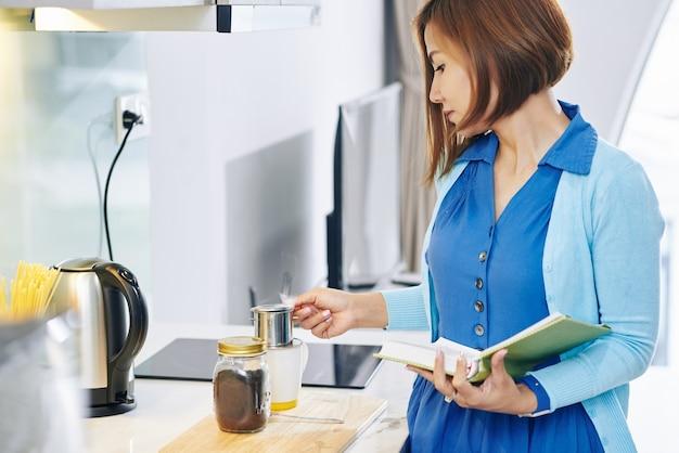 Junge vietnamesische frau mit buch in den händen, die kaffee in der küche am morgen machen