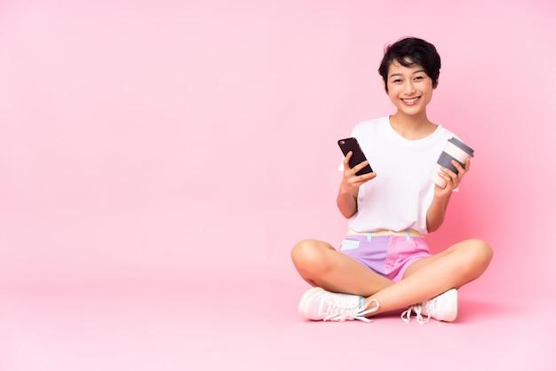 Junge vietnamesische frau mit den kurzen haaren, die auf dem boden über der isolierten rosa wand sitzen, die kaffee hält, um und ein handy wegzunehmen