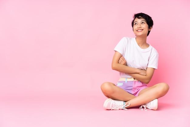 Junge vietnamesische frau mit den kurzen haaren, die auf dem boden über der isolierten rosa wand sitzen und beim lächeln nach oben schauen