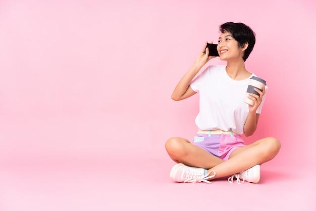 Junge vietnamesische frau mit den kurzen haaren, die auf dem boden über rosa wand halten kaffee halten, um wegzunehmen und ein handy