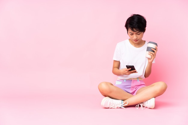 Junge vietnamesische frau mit den kurzen haaren, die auf dem boden über rosa wand sitzen kaffee halten, um weg und ein handy