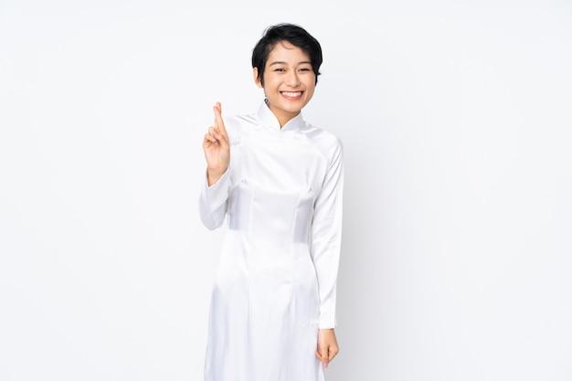 Junge vietnamesische frau mit den kurzen haaren, die ein traditionelles kleid über isolierter weißer wand mit den fingern kreuzen tragen und das beste wünschen