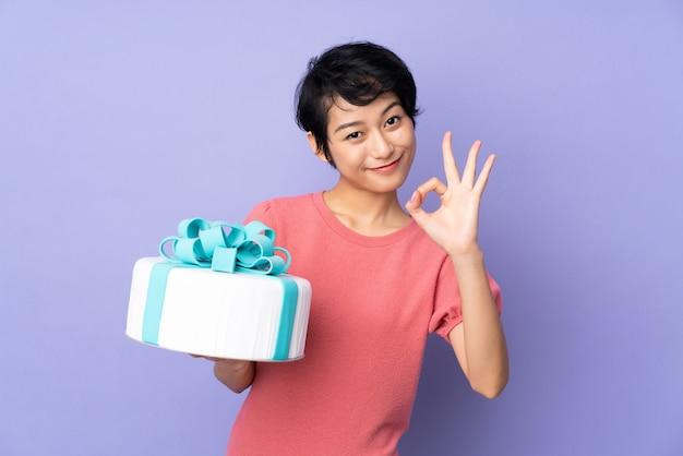 Junge vietnamesische frau mit den kurzen haaren, die einen großen kuchen über lokalisiertem purpur halten, das ok zeichen mit den fingern zeigt