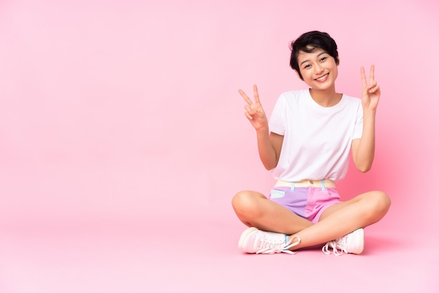 Junge vietnamesische frau mit kurzen haaren, die auf dem boden über isolierter rosa wand sitzen, die siegeszeichen mit beiden händen zeigt