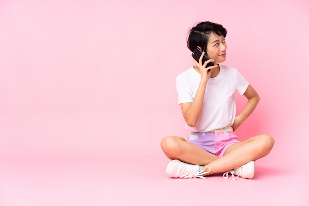 Junge vietnamesische frau mit kurzen haaren, die auf dem boden über rosa wand sitzen und ein gespräch mit dem mobiltelefon mit jemandem halten
