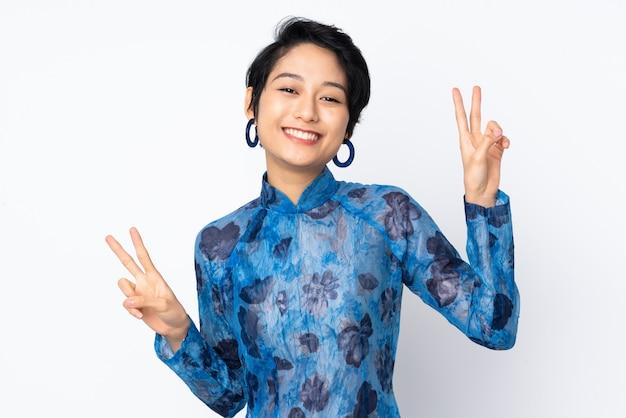 Junge vietnamesische frau mit kurzen haaren, die ein traditionelles kleid über isoliertem weiß tragen, das siegeszeichen mit beiden händen zeigt