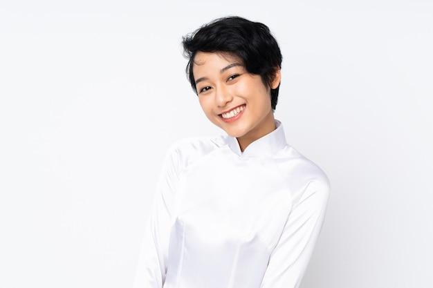 Junge vietnamesische frau mit kurzen haaren, die ein traditionelles kleid über isoliertem weiß tragen