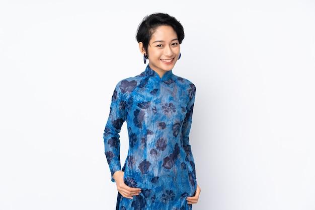 Junge vietnamesische frau mit kurzen haaren, die ein traditionelles kleid über isoliertem weißem lachen tragen