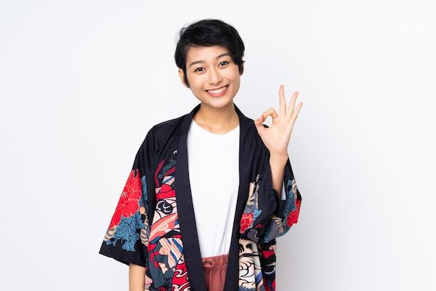Junge vietnamesische frau mit kurzen haaren, die ein traditionelles kleid über isolierter weißer wand tragen, die ok zeichen mit den fingern zeigt