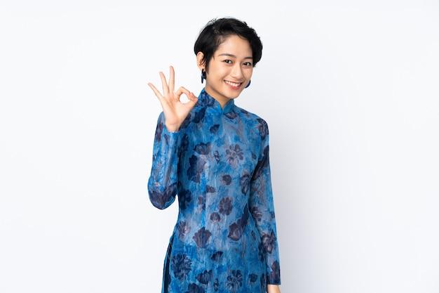 Junge vietnamesische frau mit kurzen haaren, die ein traditionelles kleid über weißer wand tragen, die ok zeichen mit den fingern zeigt