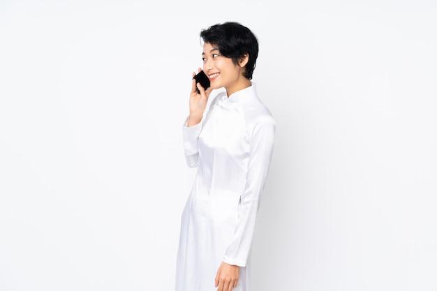 Junge vietnamesische frau mit kurzen haaren, die ein traditionelles kleid über weißer wand tragen und ein gespräch mit dem mobiltelefon mit jemandem halten