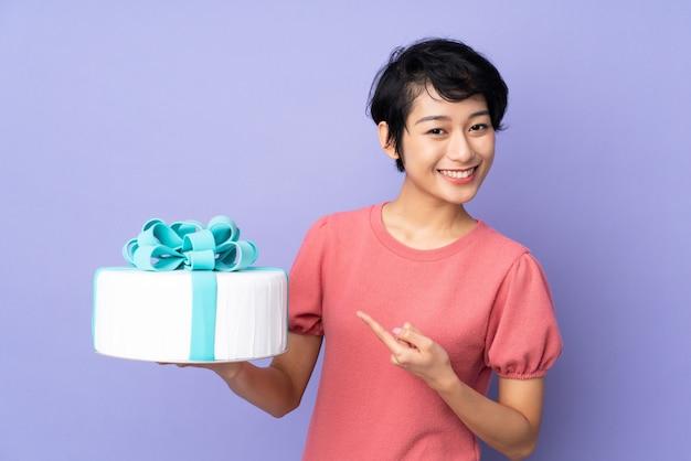 Junge vietnamesische frau mit kurzen haaren, die einen großen kuchen über isoliertem purpur halten und ihn zeigen