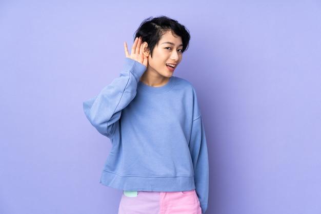Junge vietnamesische frau mit kurzen haaren über isoliertem purpur, der etwas hört, indem man hand auf das ohr legt