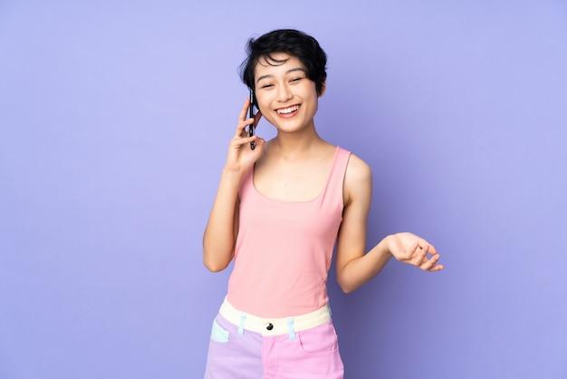 Junge vietnamesische frau mit kurzen haaren über lila wand, die ein gespräch mit dem handy mit jemandem hält
