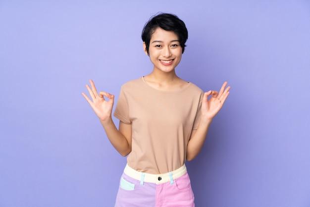 Junge vietnamesische frau mit kurzen haaren über lila wand, die ok zeichen mit beiden händen zeigt