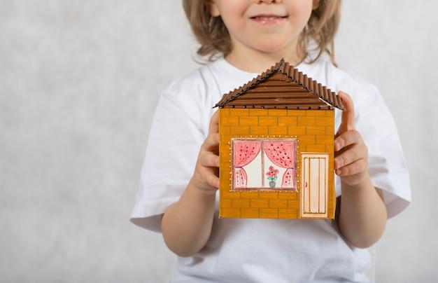 Junge von fünf jahren hält handgemachtes kartonpapierhaus. nahaufnahme