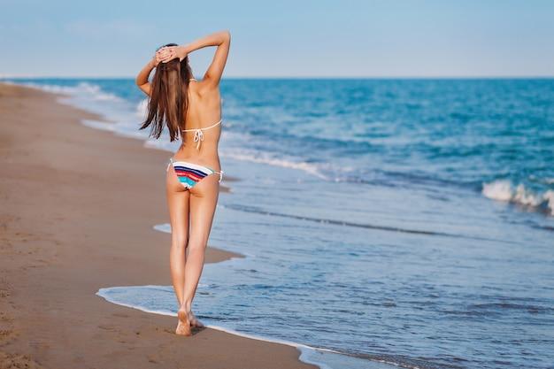 Junge vorbildliche frau in badebekleidung an der meeresküste