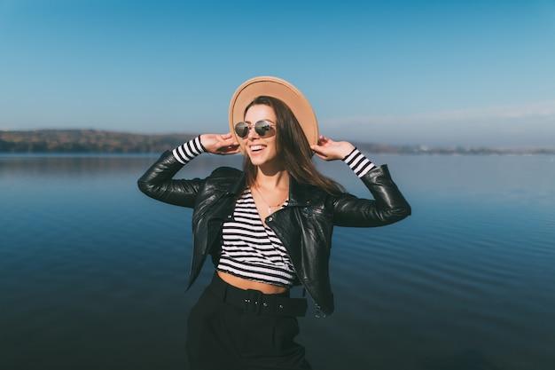 Junge vorbildliche mädchenfrau, die im herbsttag an der seewasserfront aufwirft, gekleidet in der freizeitkleidung