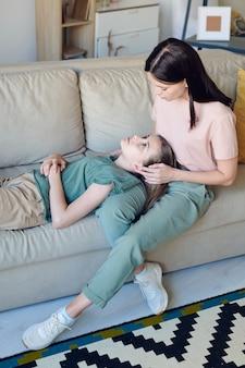 Junge vorsichtige brünette frau, die sich um ihre süße, erholsame teenager-tochter mit langen blonden haaren kümmert, während sie sich auf der couch entspannen?
