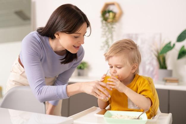 Junge vorsichtige mutter, die glas orangensaft hält, während sie sich durch ihren niedlichen kleinen sohn biegt, der es während des frühstücks durch kleinen esstisch trinkt