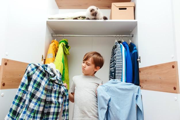 Junge wählt kleidung im kleiderschrank zu hause. netter junge, der schulhemd nimmt, um zu tragen.