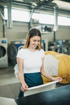 Junge wäscherei-arbeiter klopfen die wäsche auf dem automaten in der chemischen reinigung.