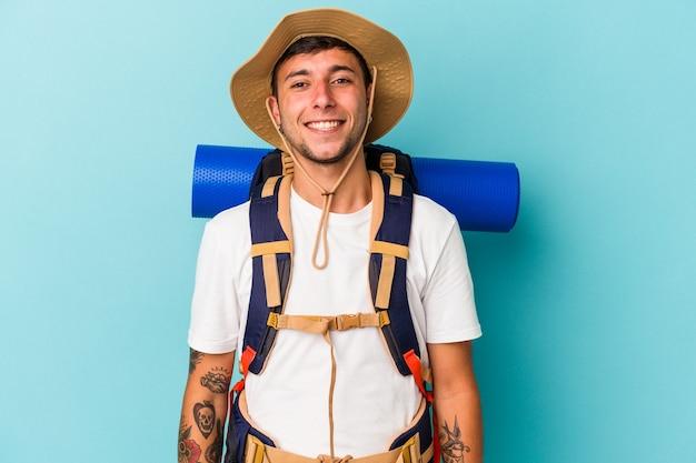 Junge wanderer mann mit hut auf blauem hintergrund isoliert glücklich, lächelnd und fröhlich.
