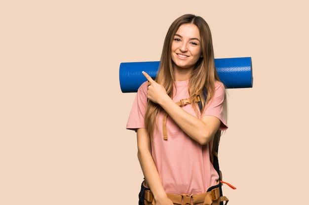 Junge wandererfrau, die auf die seite zeigt, um ein produkt auf lokalisierter gelber wand darzustellen