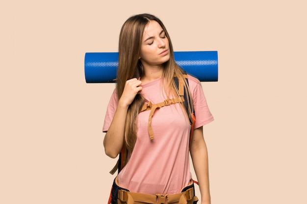 Junge wandererfrau mit müdem und krankem ausdruck auf lokalisiertem gelbem hintergrund