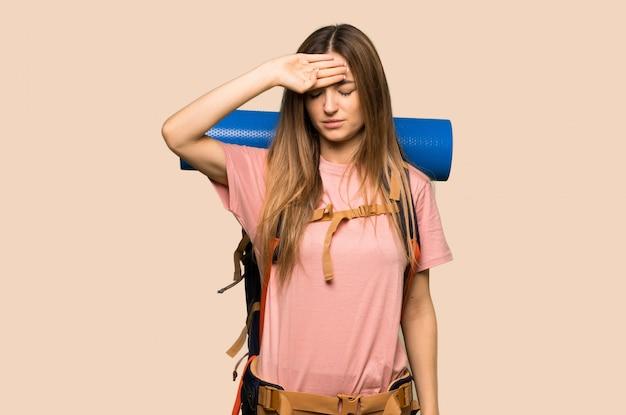 Junge wandererfrau mit müdem und krankem ausdruck auf lokalisierter gelber wand