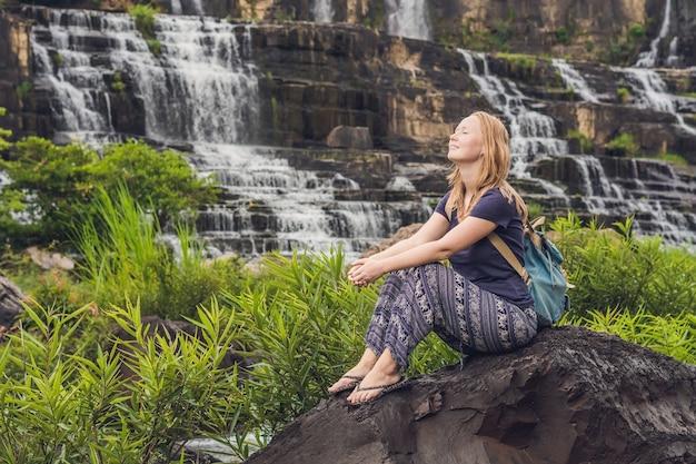 Junge wandererin, touristin auf der oberfläche des amazing pongour waterfall ist berühmt und der schönste herbst in vietnam