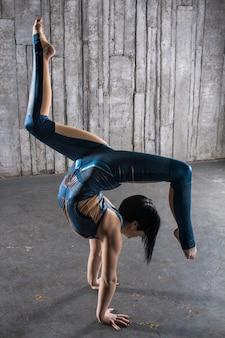 Junge weibliche acrobat stehend auf grauem hintergrund im fotostudio. flexibler frauen-zirkus-turner, gymnastik-handstand.
