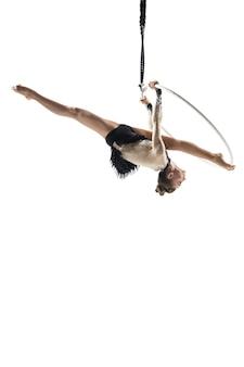 Junge weibliche akrobatische zirkussportlerin isoliert auf weiß ausbalanciert