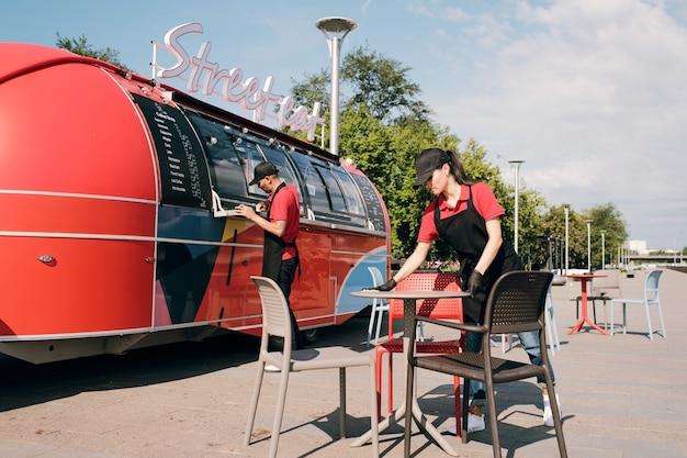Junge weibliche angestellte des imbisswagen-reinigungstisches