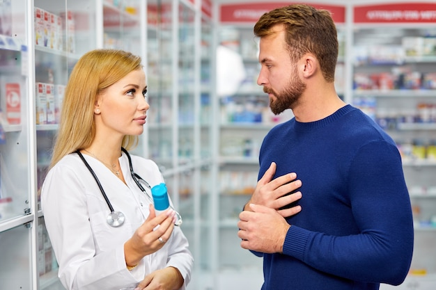 Junge weibliche apothekerin mit droge und männlichem kunden an der apotheke