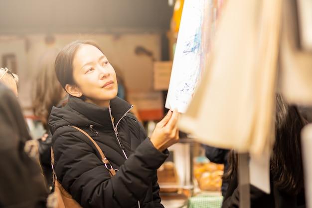 Junge weibliche asiatische touristische frau, die kleidung auf straßenmarkt kauft und wählt.