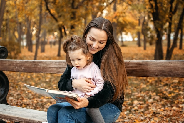 Junge weibliche babysitterin und kleinkind-baby las buch im herbstpark glückliche familienmutter und