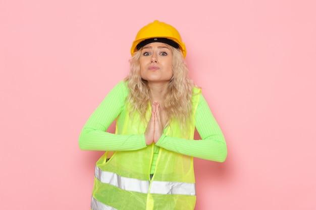 Junge weibliche baumeisterin der vorderansicht im gelben helm des grünen bauanzugs, der gerade betend auf dem baujob der rosa raumarchitektur aufwirft